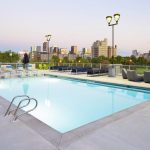 Rooftop pool surrounded by seating with downtown skyline in background.