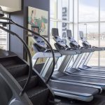 Interior of fitness center with treadmills and stair climbing machines.