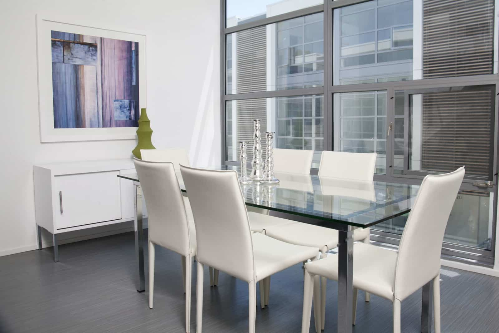 Interior of dining area with glass and steel table and white leather chairs.