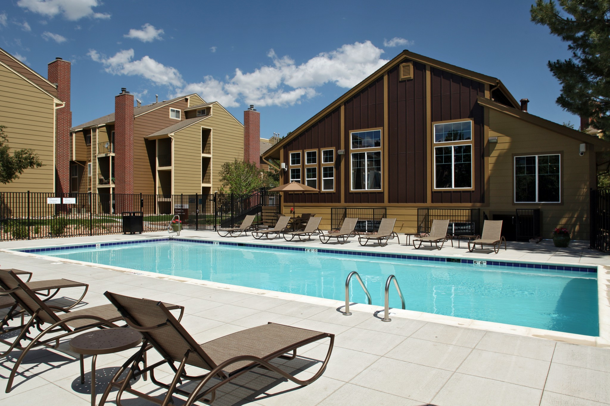 Outdoor pool area with lounge chairs and apartment building in the background.
