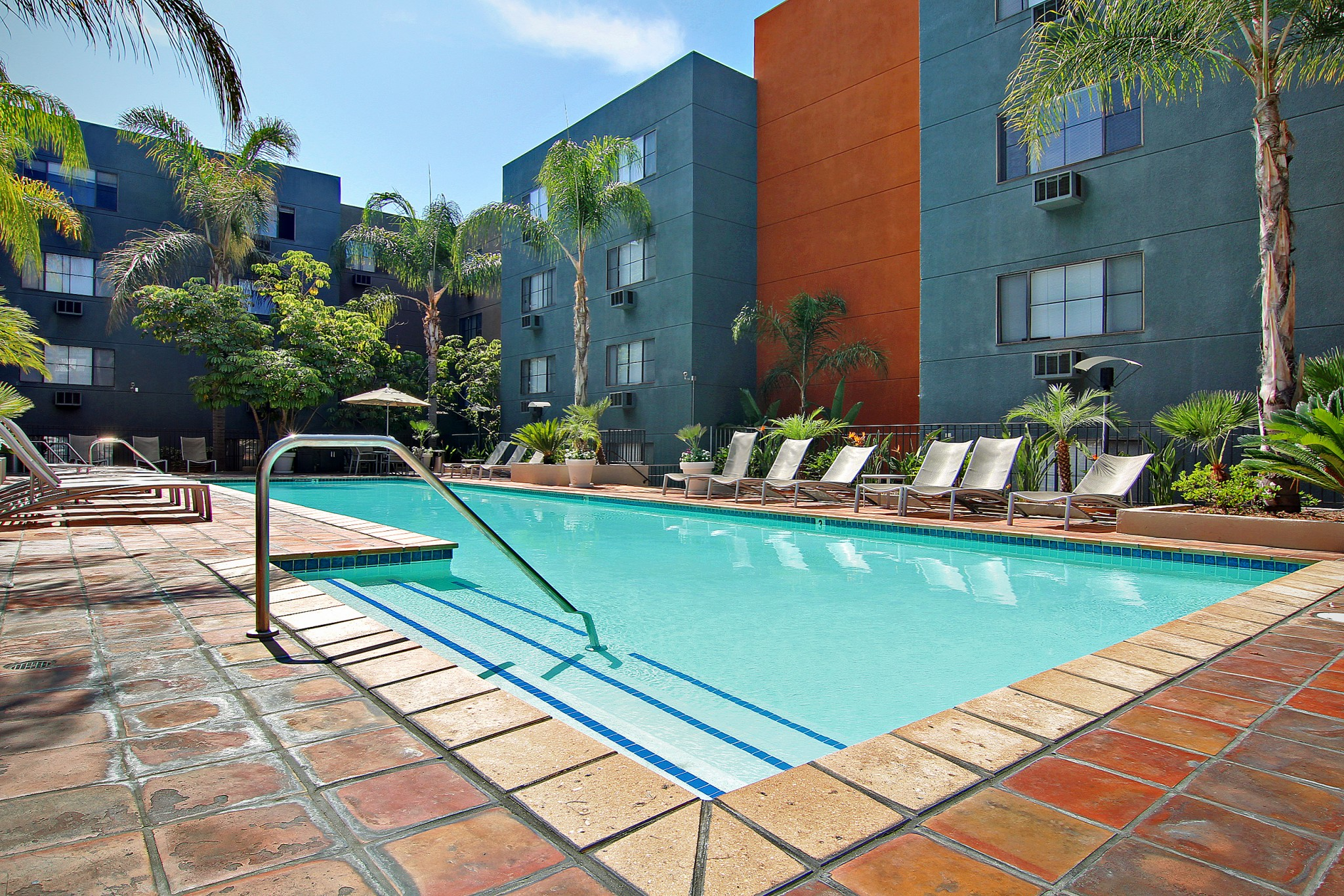 View of courtyard pool with lounge chairs, trees, and building in the background..
