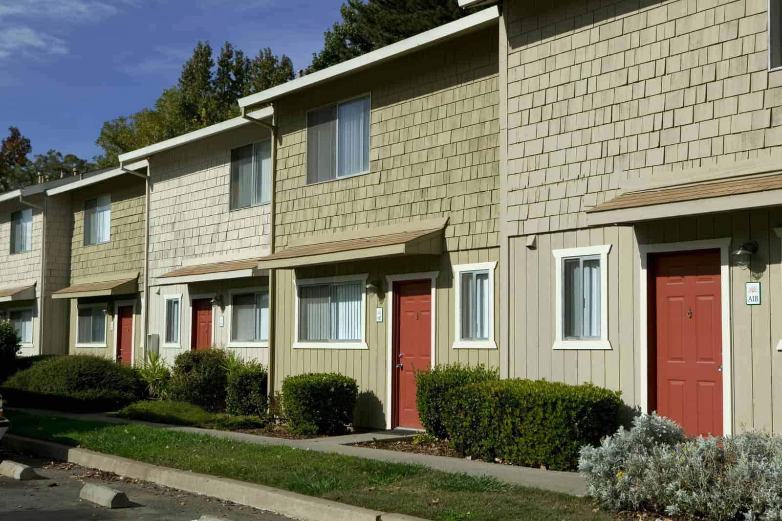 Exterior of 2 story units with red doors.