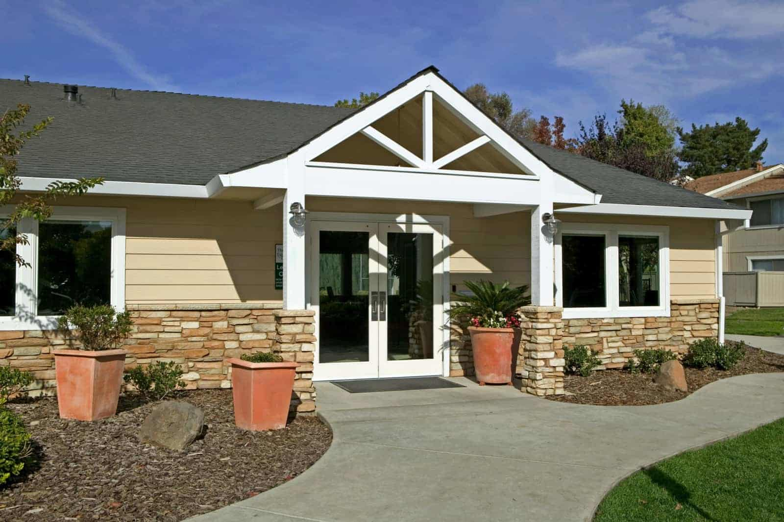 Exterior view of single story clubhouse building with double door entrance.
