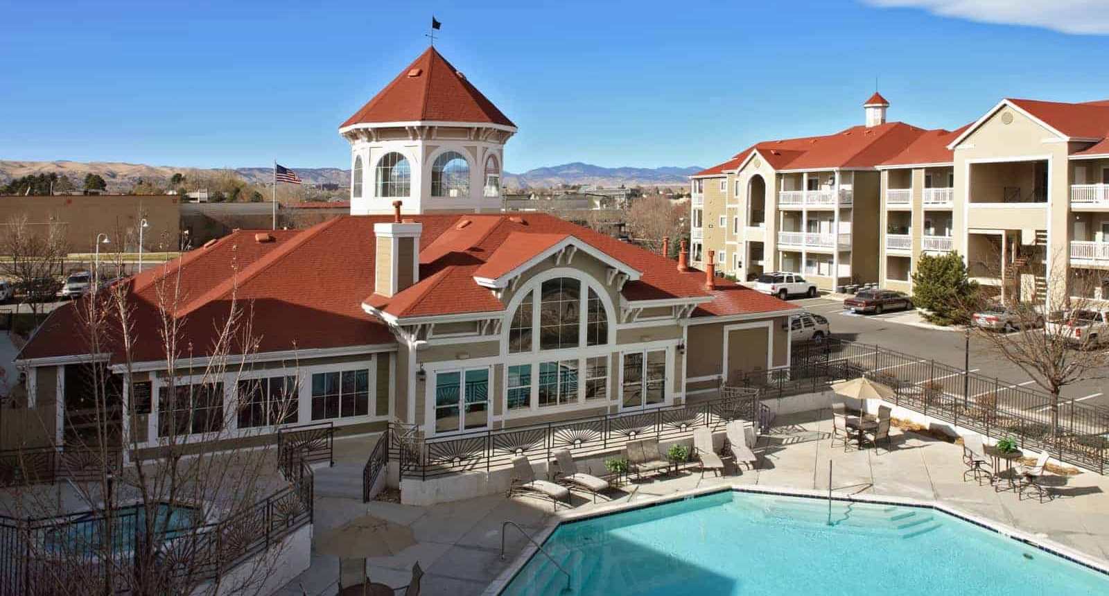 View of the apartment complex with pool in the foreground.