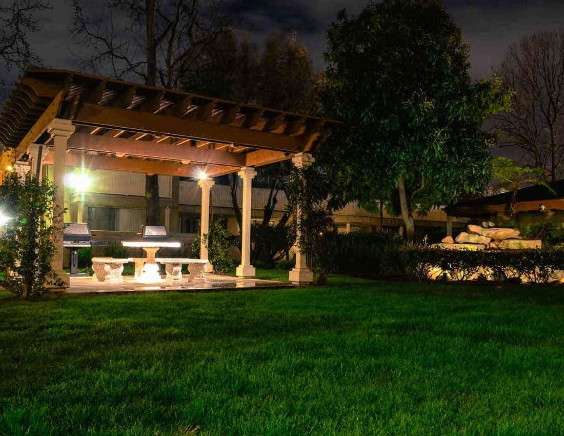 View of the bbq grills, picnic table, and trellis at night.