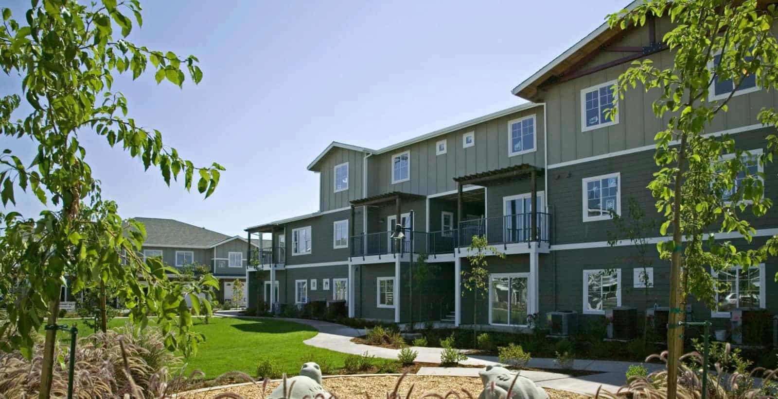 Exterior of 3 story apartment building with a lawn and landscaping in the foreground.