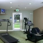 View of the fitness center with 3 cardio machines and a TV.