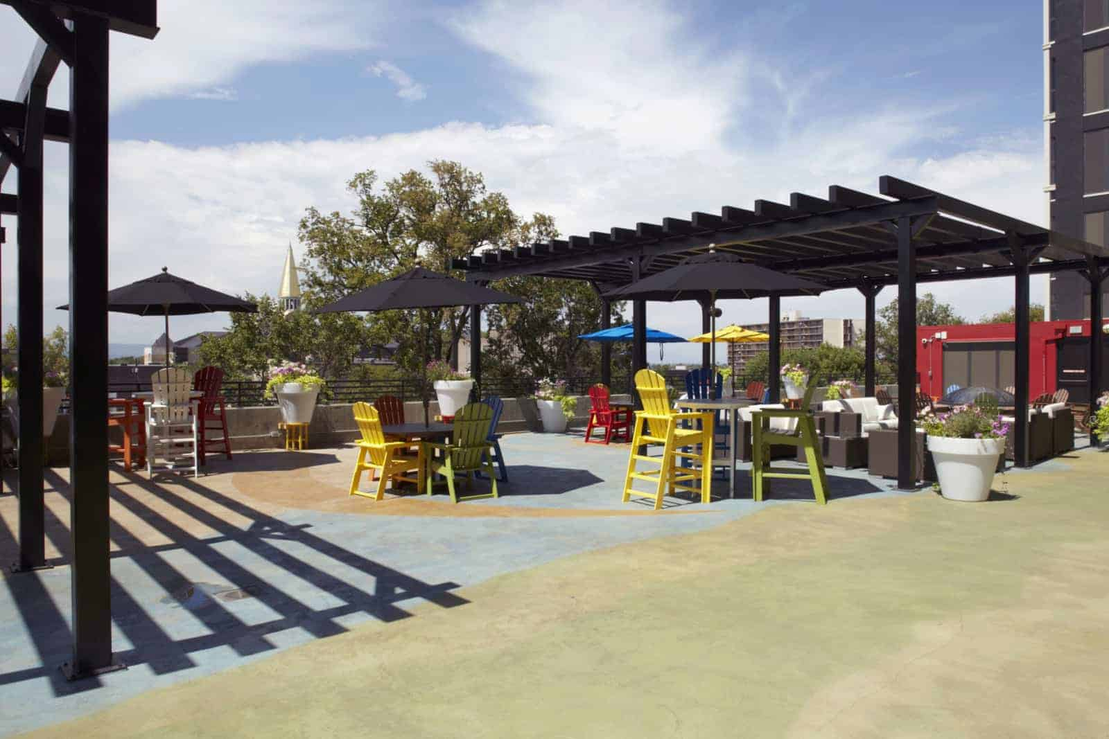 Roofdeck with adirondack chairs and barstools, couches, tables, umbrellas, and trellis.