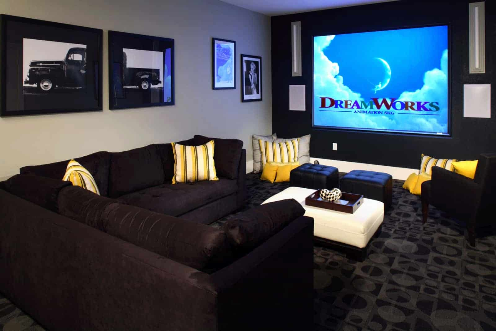 Theatre room with couches, and ottomans.