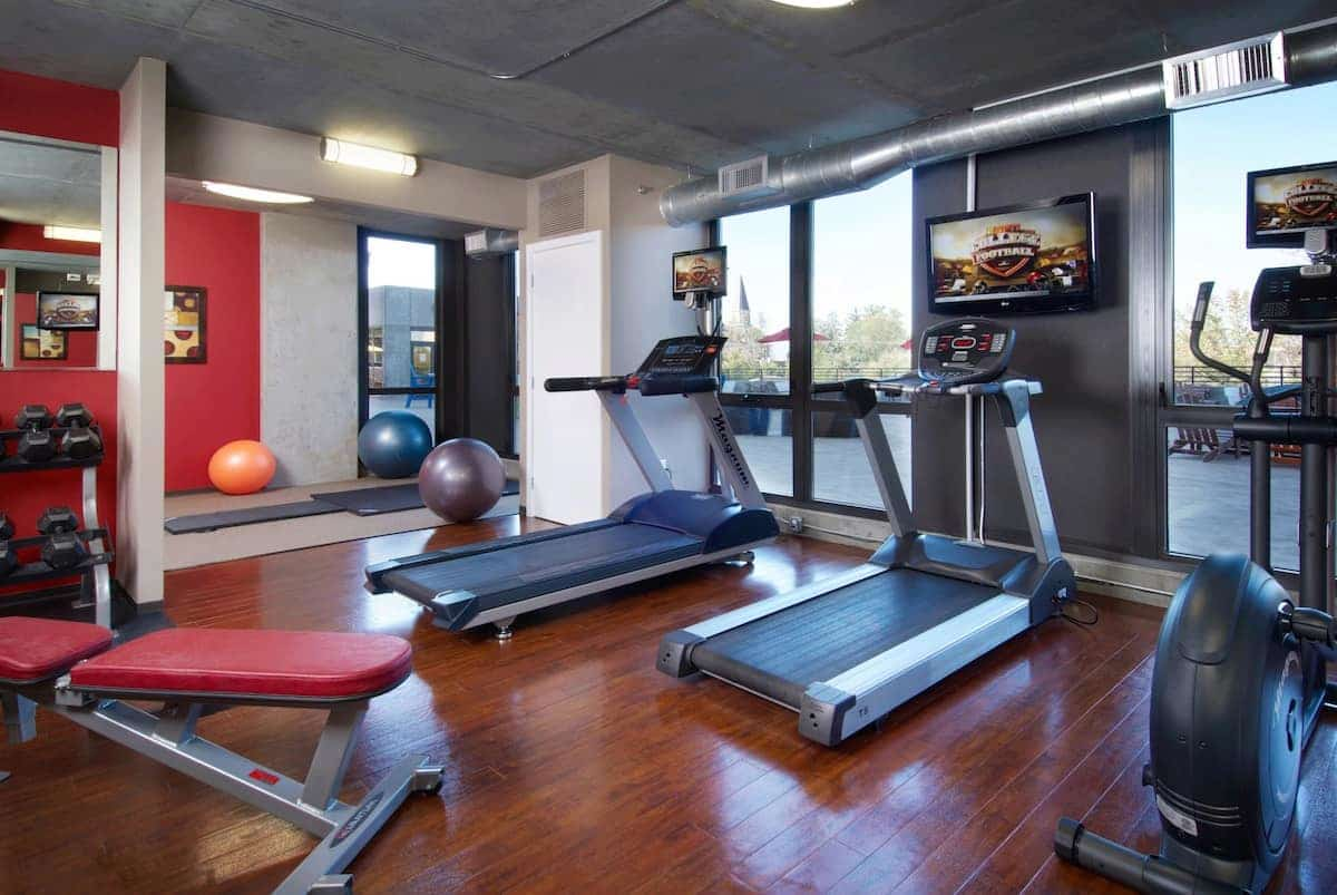 Fitness center with several exercise machines, dumbbells, and physio balls.