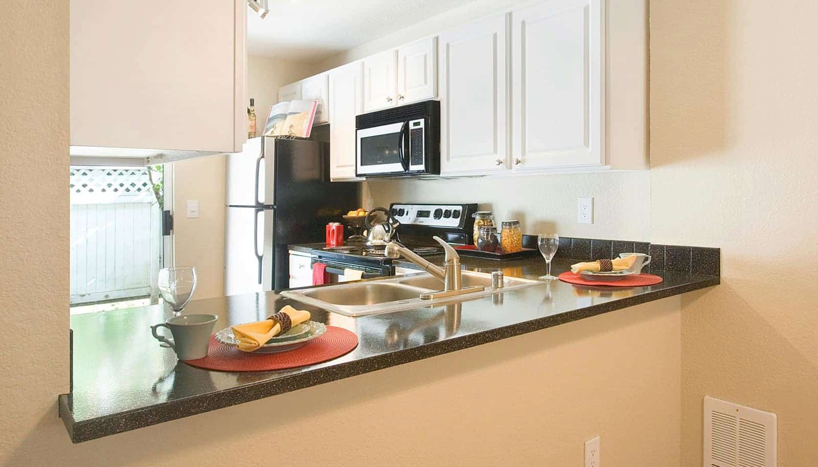 Ktichen with stainless steel appliances, black countertops, and white cabinets.