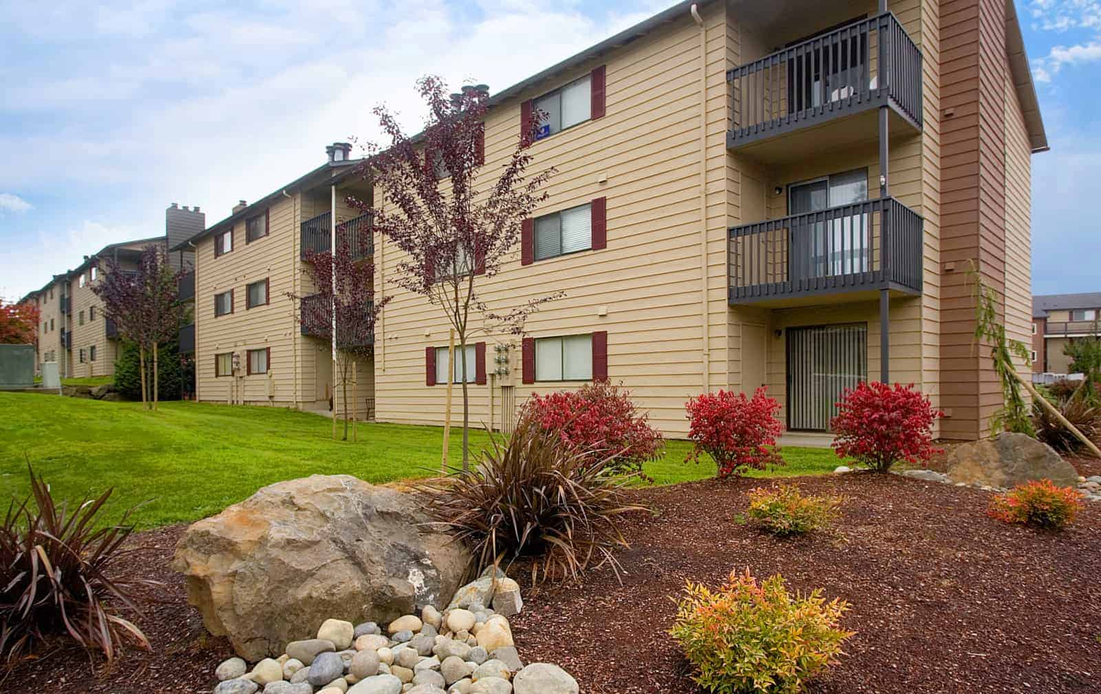 Exterior of 3 story apartment building with balconies and landscaping in the foreground.