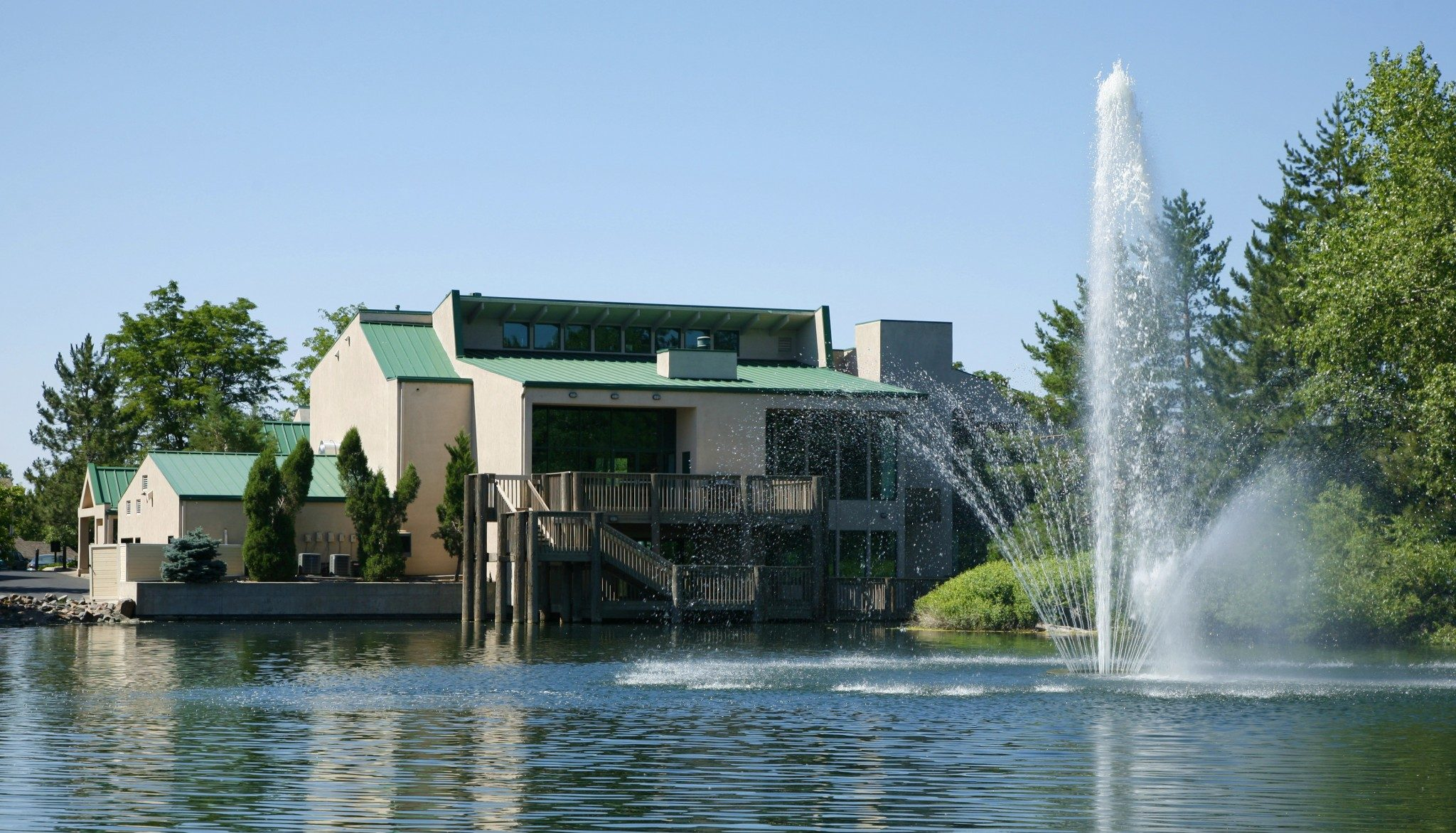 View of lake and fountain with building and trees in the background.