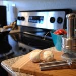 Close up of garlic press and garlic on cutting board on the kitchen counter with the stove in the background.