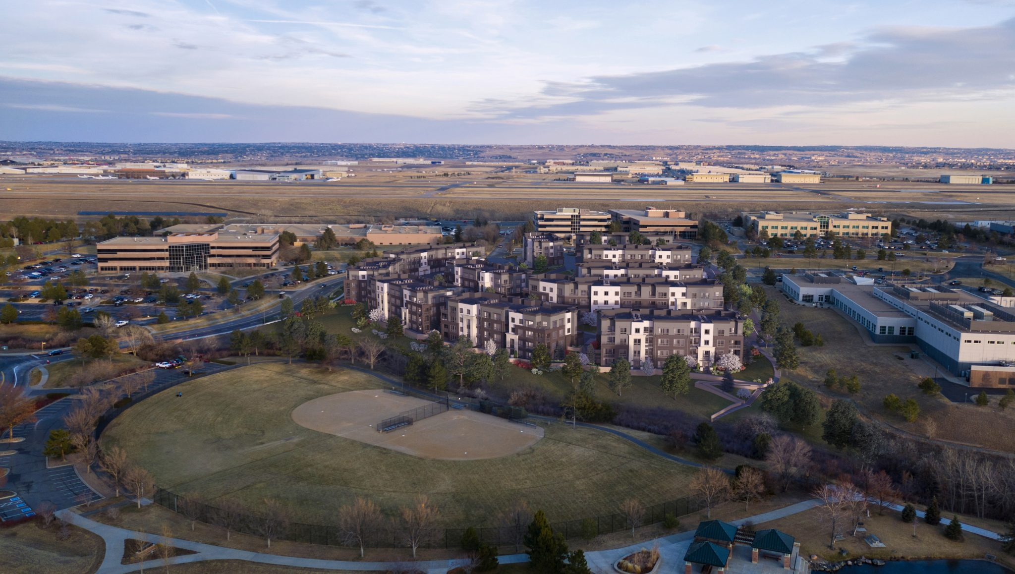Aerial exterior of entire apartment complex with baseball fields in the foreground and horizon in background