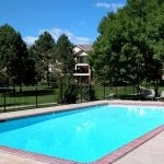Outdoor pool surrounded by lawn and trees and apartment buildings.