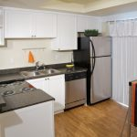 Apartment kitchen with stainless steel appliances, black countertop and white cabinets..