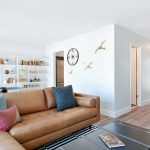 Apartment living room interior with leather couch and bookshelves