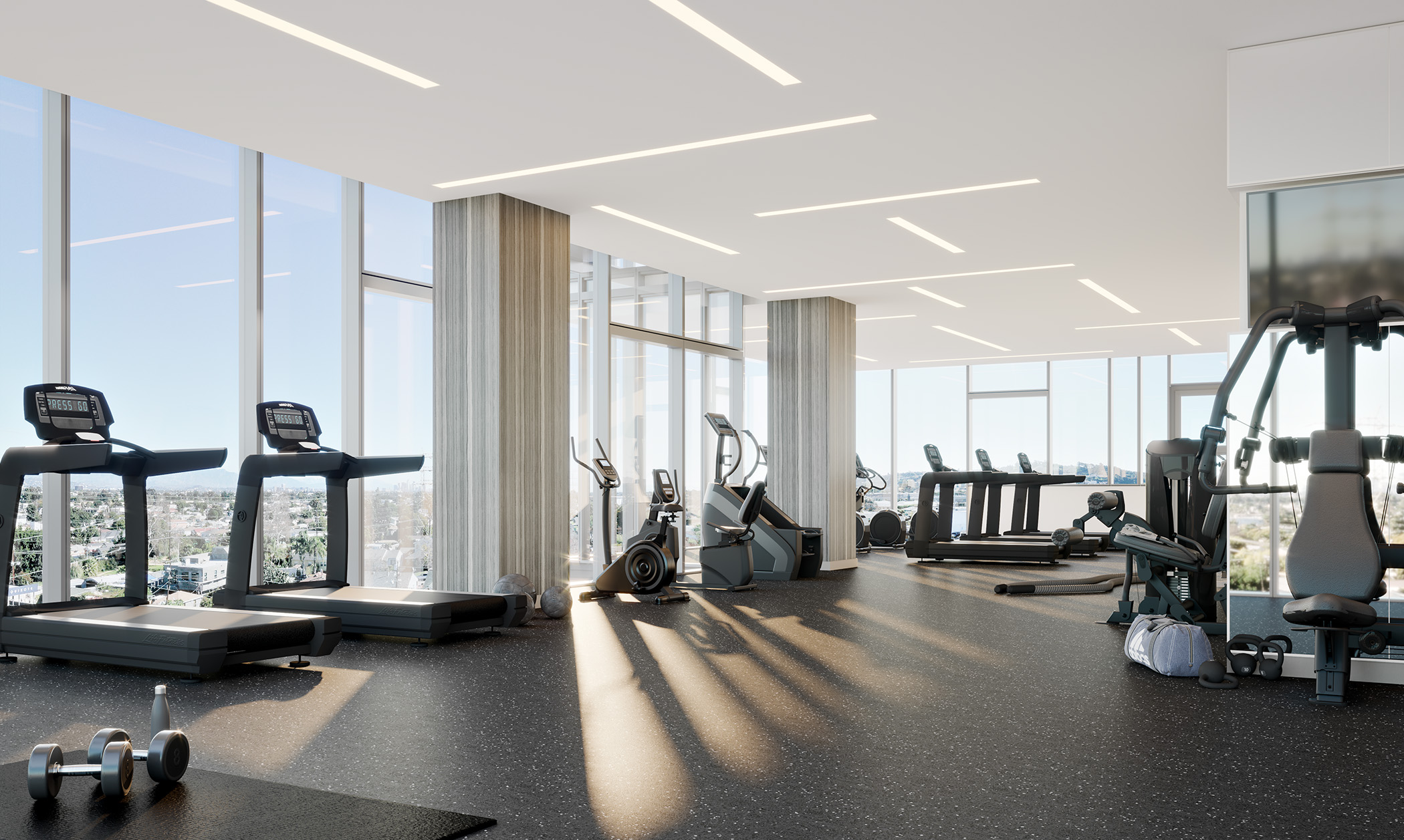 Interior of fitness room with various exercise machines and floor to ceiling windows.
