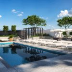 Exterior of rooftop pool deck with pool, lounge chairs, sun umbrellas, and trees with city views in background